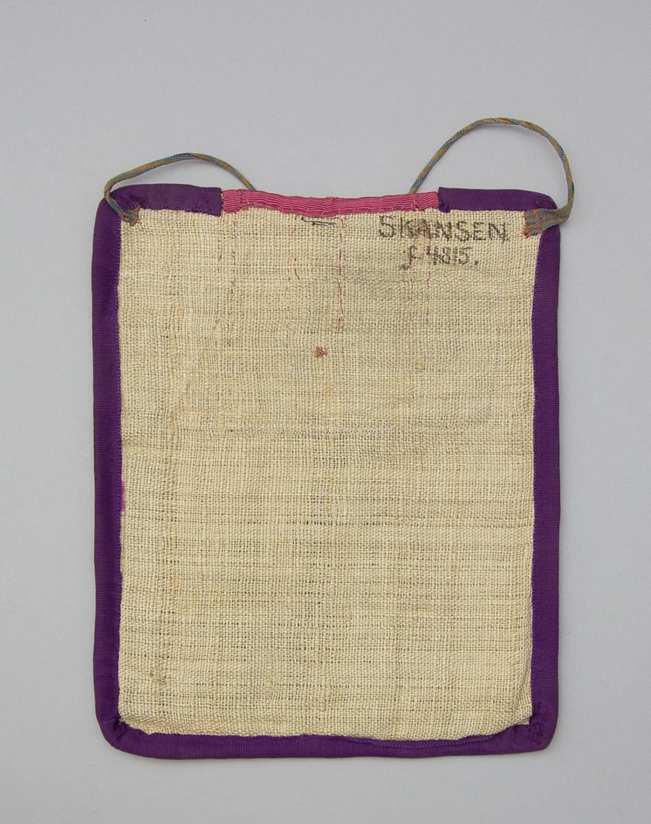 Kjolväska, fyrkantig modell med bågformad öppning upptill. Skarvad av tre sidentyger, i mitten  rosa  rips och vid sidorna mönstervävt i guldgult  på svart botten.  Fickan fodrad med vitt bomullstyg. Dolt av ripsbandet sitter ett tidigare använt knapphål. Kantad runtom med lila ripsband. Baksida av grovt och glest linne Midjeband av bomull,  randiga i gult och blått.