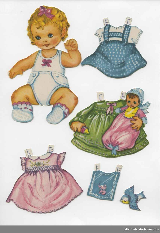 """Klippdocka med kläder och tillbehör från 1950-talet. Docka och kläder märkta """"Eva"""" - dockans namn.Dockan, av papp, föreställer en baby, med blont hår, iklädd linne, tygblöja och sockar. Garderoben består av tre  klänningar, pyjamas och ett vinterplagg med kapuschong. Dockan har dessutom tillbehör som hakklapp och leksaker (bollar, klossar, skallror, mm). Vissa föremål är märkta både """"Eva"""" och """"Dan"""" (MM 04588)."""