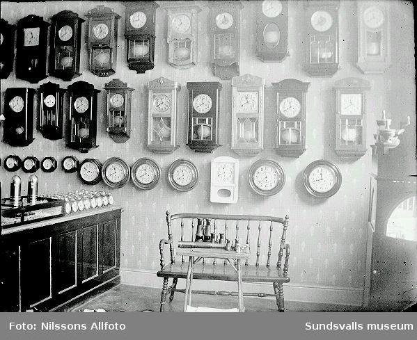 Interiör från en uraffär, klockor hänger på väggen.