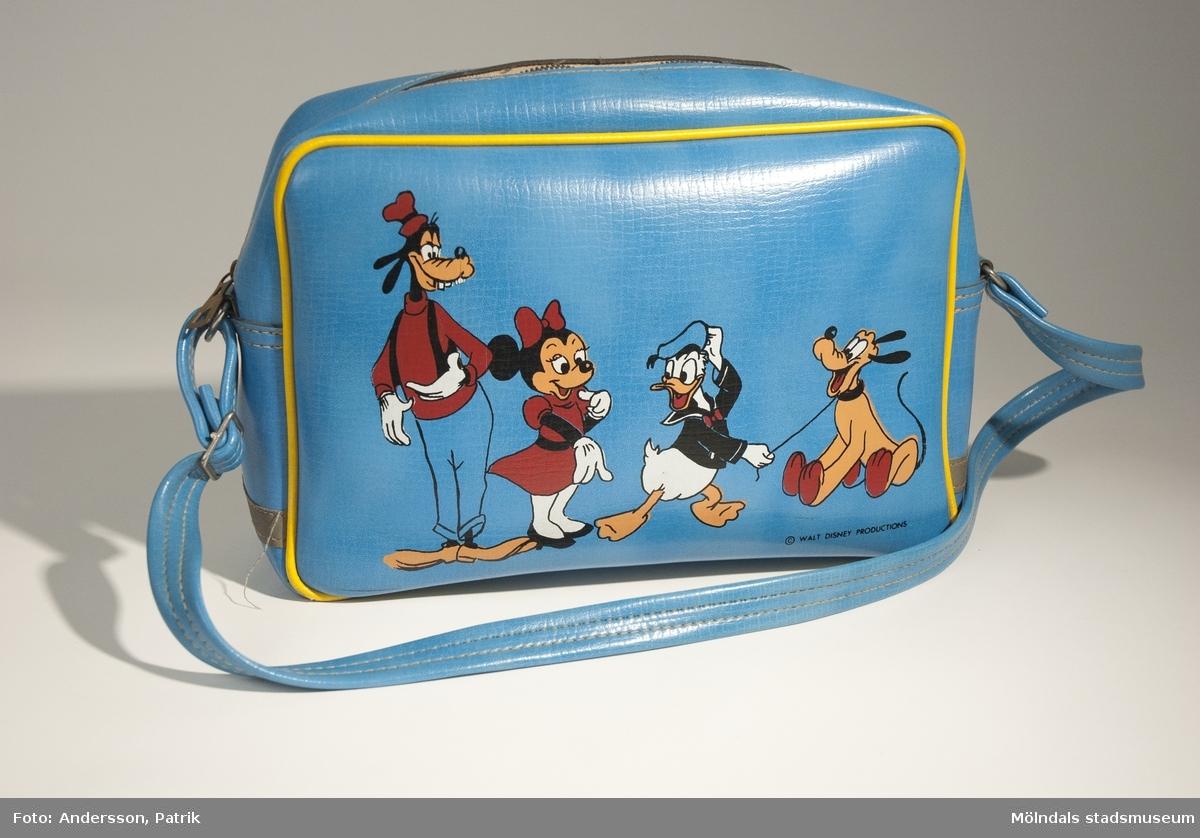 """Blå väska med disneymotiv. Den användes förmodligen som skolväska under 1970-talet. Den är något sliten.Väskan är blå och har en gul smal rand runt om, på varje långsida. Den har också ett axelband. På ena långsidan av väskan finns 4 st. disneyfigurer: Långben, Mimmi Mouse, Kalle Anka och Pluto som mönster. Längst ner i högra hörnet står också """"WALT DISNEY PRODUCTIONS"""" tryckt med svarta bokstäver. På båda kortsidorna av väskan finns en smal grå remsa fastsydd som fungerar som reflex. Remsan är i samma material som resten av väskan.Väskan har ett fack och detta stängs med dragkedja.  Innefodret är svart.MåttBredd: cirka 300 mm, Höjd: cirka 215 mm, Djup: cirka 95 mm Axelband, Längd: 78 mm, Bredd: 20 mm"""
