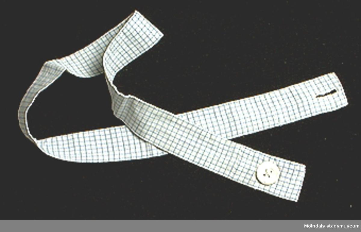 Blårutigt förkläde (21948:1), sytt som klänning med breda axelband och skärp. Broderat motiv i korsstygn mitt på livet.Förklädet något gulnat framtill. Tillhörande skärp med knapp och knapphål (21948:2).