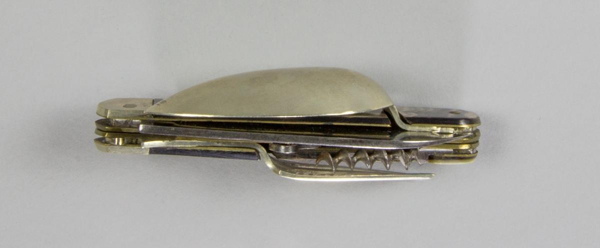 Bestick, fällkniv med handtag av horn och knivblad av stål, sked och gaffel av försilvrad metall, samt dessutom korkskruv och handskknäppare. Signerad: '59 Sauvagnat'.