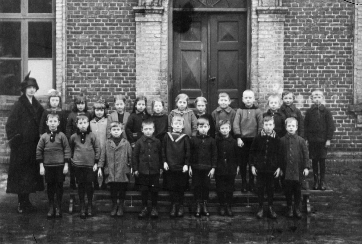 Lärarinnan Agda Karlsson med elever. Flickor och pojkar uppställda framför Grevedämmets skolas port.