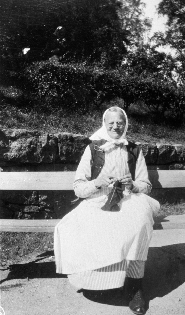 Äldre kvinna som sitter på en bänk vid Kärra Hökegård, ett försörjningshem för såväl senildementa som psykiskt sjuka, utvecklingsstörda och ensamstående mödrar. Verksamheten försvann i och med att Lackarebäckshemmet stod klart 1951.