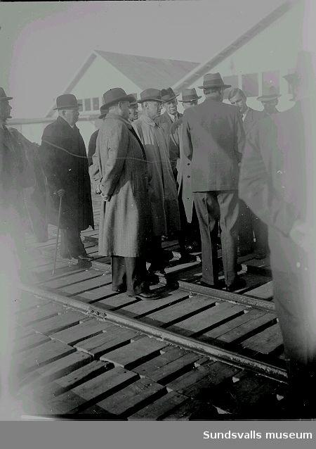 Män samlade vid ett magasin, tågräls.