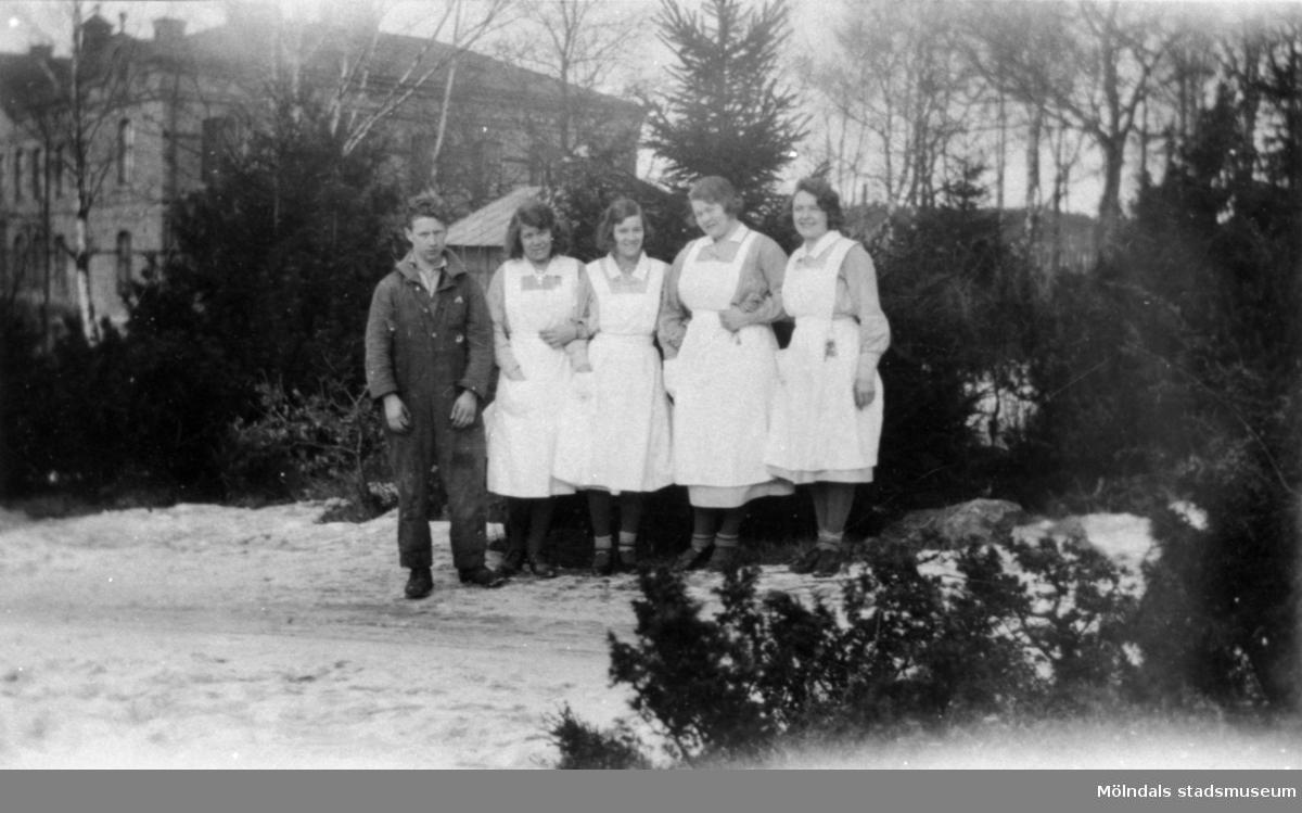 Sköterskor i armkrok på Stretereds skolhem, julen 1932.  De står med huvudbyggnaden i bakgrunden. Det är jultid med huggna julgranar, som väntar på att placeras ut i de olika avdelningarna. Det skulle kunna vara en ung Johan Karlsson som uppvaktar damerna. Platsen är vägen upp mot rättarstugan. Eftermiddagssolen står lågt.