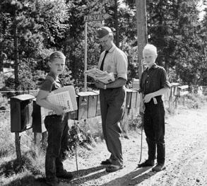 Bilåkande lantbrevbäraren Erik Johansson på linjen Åkersberga - Singö - Björnhuvud - Åkersberga. Lantbrevbärare Johansson lämnar post vid brevlådesamlingen i Alsvik.  Foton augusti 1961.