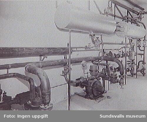 Sundsvalls gasverk togs i bruk 5/12 1867 och drevs som kolgasverk fram till den 19/7 1951. Från juli 1951 övergick gasverket till distribution av en blandgas gasol och luft. Här syns pumpar och instrumentering m.m. i gasolstationen, 20 augusti 1951.