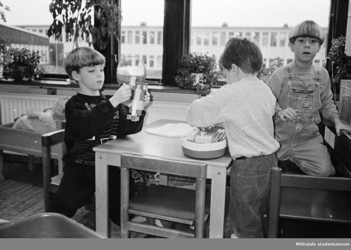Tre pojkar sitter vid ett barnbord och leker med Duplo-lego. Vid sidan av dem står en docksäng. I bakgrunden syns fönster med Åbyskolans fasad. Katrinebergs daghem, 1992.