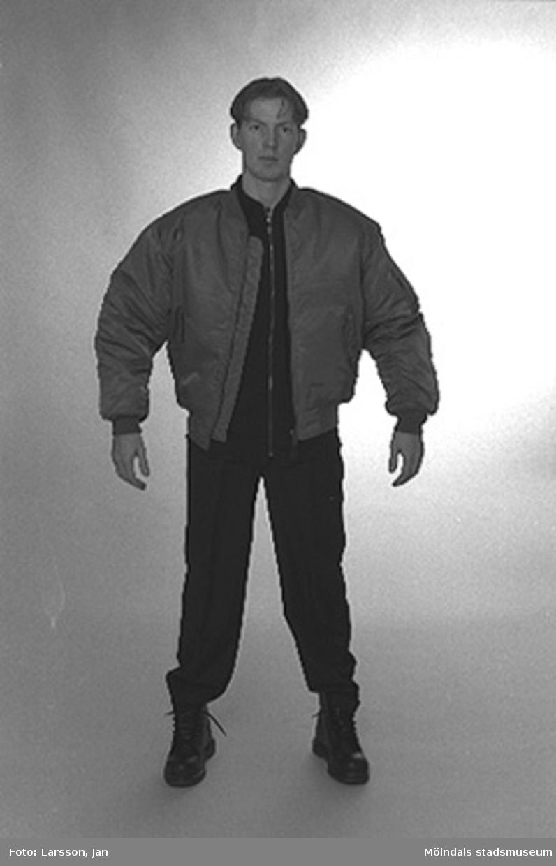 """Joakim Hjalmarsson iförd Bomberjacka, finbyxor och Dr. Martenskängor inför utställningen """"Krinoliner och kortkort"""" på Mölndals museum 1994-12-05."""