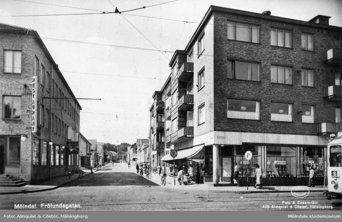 """Vykort """"Mölndal. Frölundagatan"""" med vy från Göteborgsvägen-Kungsbackavägen, 1940-tal. Till vänster skymtar Gillet eller Hantverkshuset (Frölundagatan 1 och Kungsbackavägen 2). Till höger ses Centrumhuset (Göteborgsvägen 1-5)."""