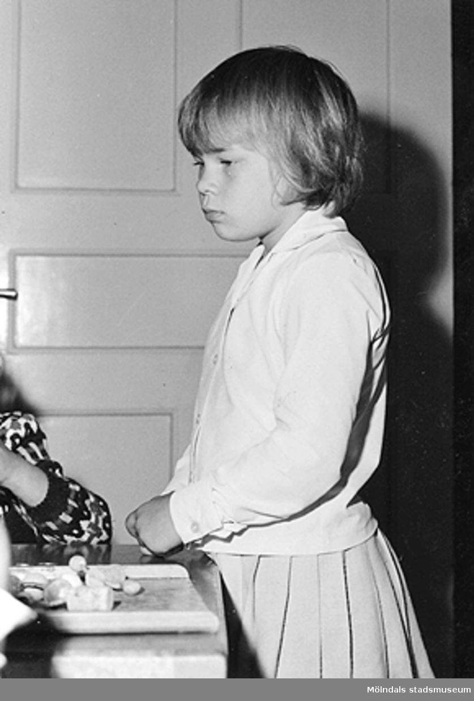 En flicka står vid sidan av ett bord. Holtermanska daghemmet 1953.