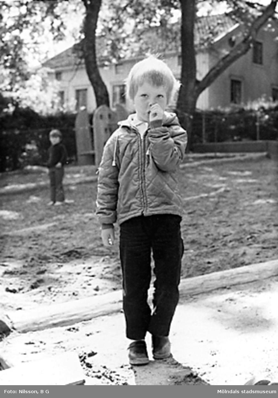 Ett barn som står utomhus vid Holtermanska daghemmet juni 1973.