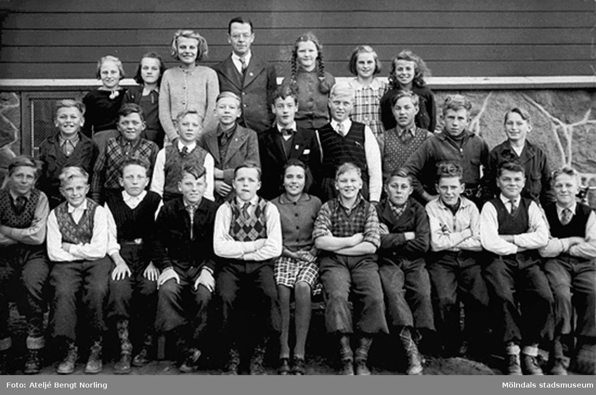 Sjunde året, ht 1939 eller vt 1940. Barnen är fotograferade mot väggen av den gamla skolbyggnaden. Övre raden: Rut Larsson, Inger Sjögren, Irma Floman, magister Sven Flodén, Gulli Andersson, Ulla Segerholm, Kate Andersén. Mellersta raden: Rune Rydén, Per Johansson, Per Olof Berntsson, Rune Andersson, Rolf Fant, Allan Hultgren, Elon Stoltz, Knut Andersson, Evert Hulterström. Främsta raden: Helge Andersson, Rune Olsson, Stig Andersson, Jean Brandin, Rune Johansson, Anna Lisa Östling, Gert Larsson, Åke Örn, Rolf Magnusson, Hilmer Karlsson, Rune Claesson.Fotot märkt 7 på baksidan.