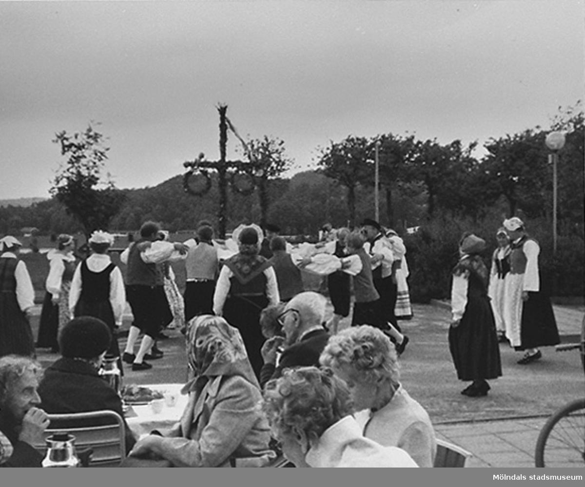 I förgrunden sitter några personer vid bord. I bakgrunden dansar ett folkdanslag runt midsommarstången. Okänt årtal.