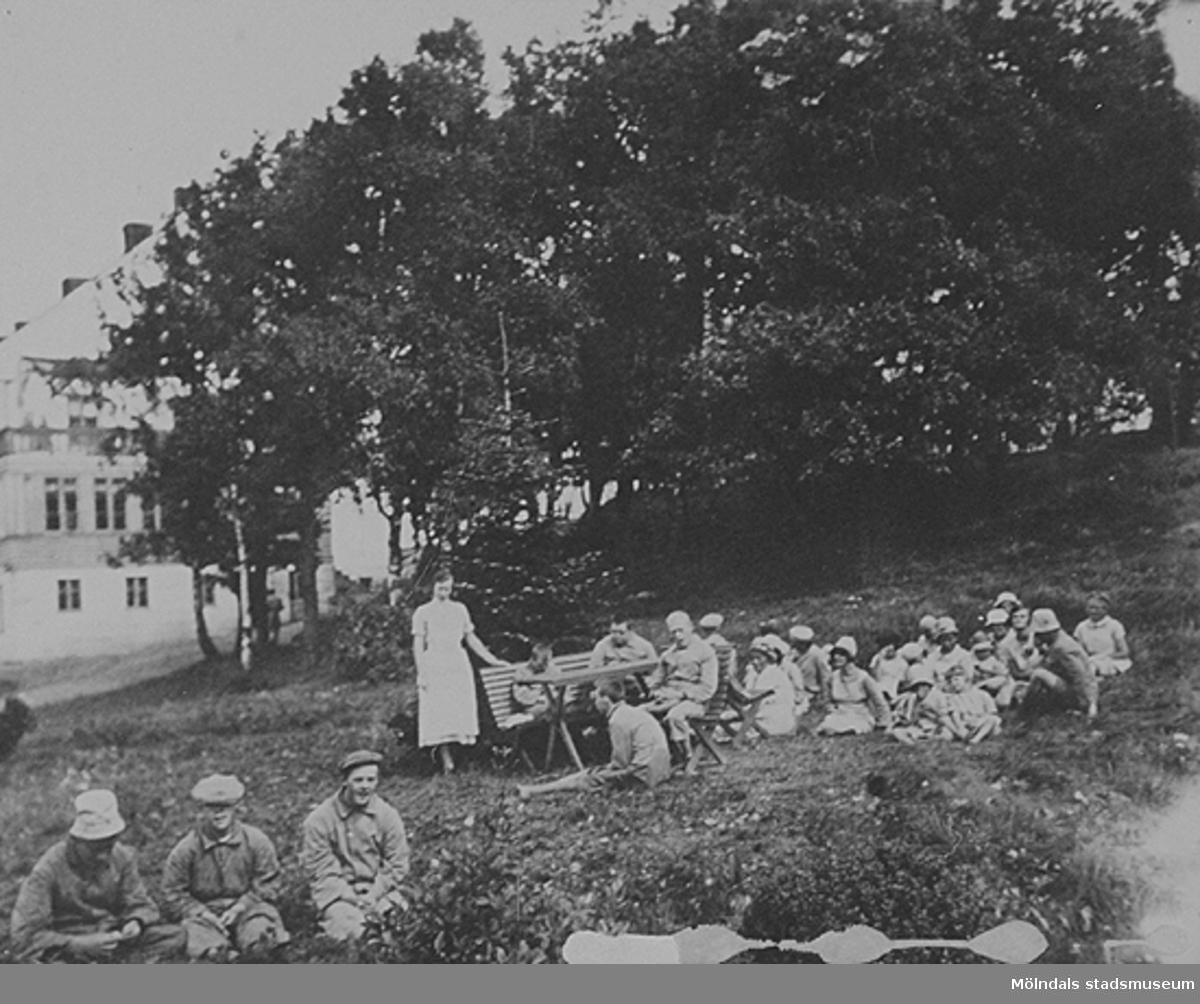 Pojkar och flickor som sitter på gräsmattan utanför asylbyggnaden. Okänt årtal.