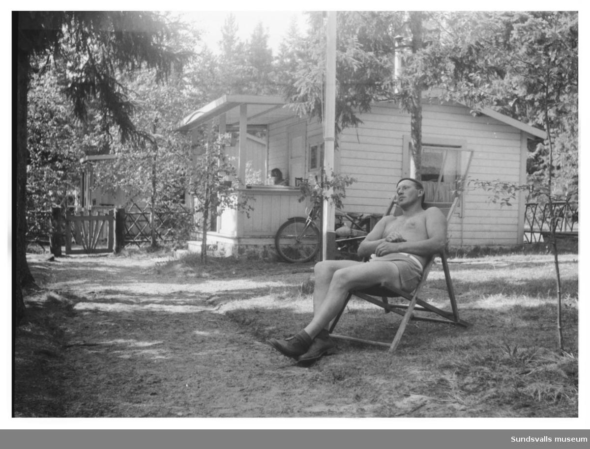 Viktor Lindqvist kopplar av i solstolen vid sommarstugan i Tranviken. Stugan har fått tak över altanen. Tomten har fått grind och staket och späda björkar har planterats runt stugan. I bakgrunden syns grannens stuga, ägare är Viktors bror Alfred Lindqvist med hustru Gunvor och son Benny.