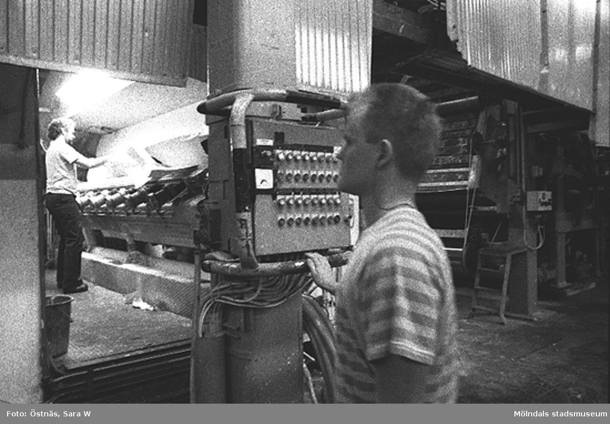 Två män i arbete. KM 2, byggnad 6. Mannen på maskinen är Juris Kuvalds och mannen i förgrunden är Lars Neckén.Bilden ingår i serie från produktion och interiör på pappersindustrin Papyrus.