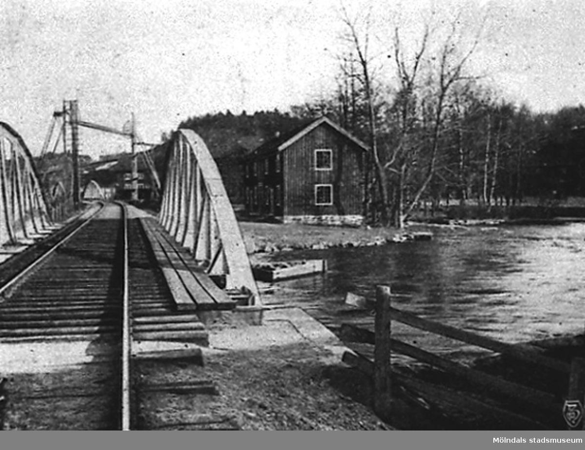 """Bro öfver Mölndalsån. Järnvägsbron öster om Carlsfors fabriker (Kvarnfallet 31) och öster om Grevedämmets skola.Avfotograferade ur """"en resa med Borås - Alfvesta järnväg,"""" G.Windy Rosenberg 1989."""