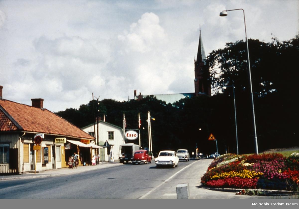 Affärbyggnader längs Frölundagatan i Mölndal, år 1965.Fässbergs kyrka i bakgrunden.
