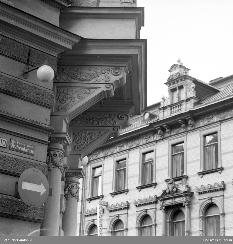 """Gatubilder från Nybrogatan i Stenstaden. Hotell Continental, """"Trean"""", ölkafé som ingick i Sundsvalls Kafé AB, Lilla Hotellet, Ejes parfymeri, Ido kaffehandel, Centrum radio med flera butiker samt exteriördetaljer på fasaderna."""