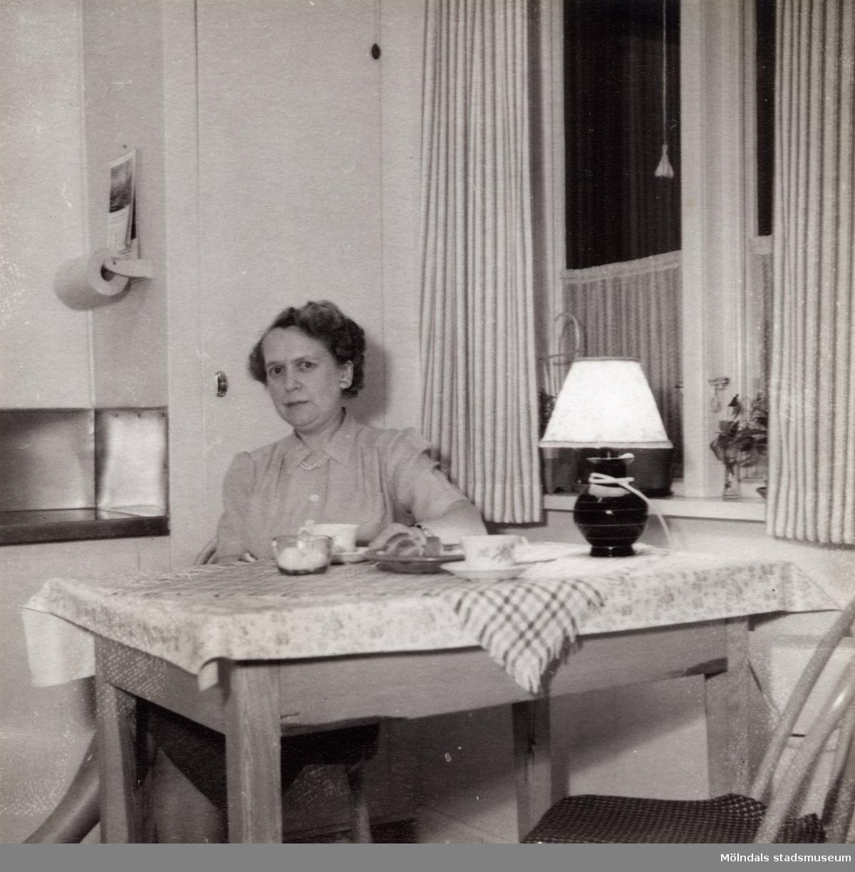 Inga-Lill Börjesson vid köksbordet på 1950-talet. Fotografi innan kylskåp installerats. Se även MMF2013:0049.