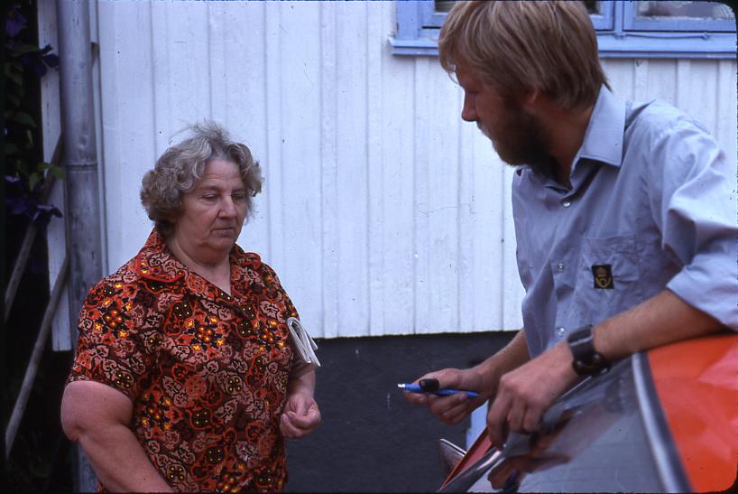 Lantbrevbäraren Mikael Mattsson besöker Maj-Britt Wessberg i Räfsta i Vallentuna. De står utanför huset, hon har en tidning under armen och han lutar sig mot bilen, med en penna i handen.