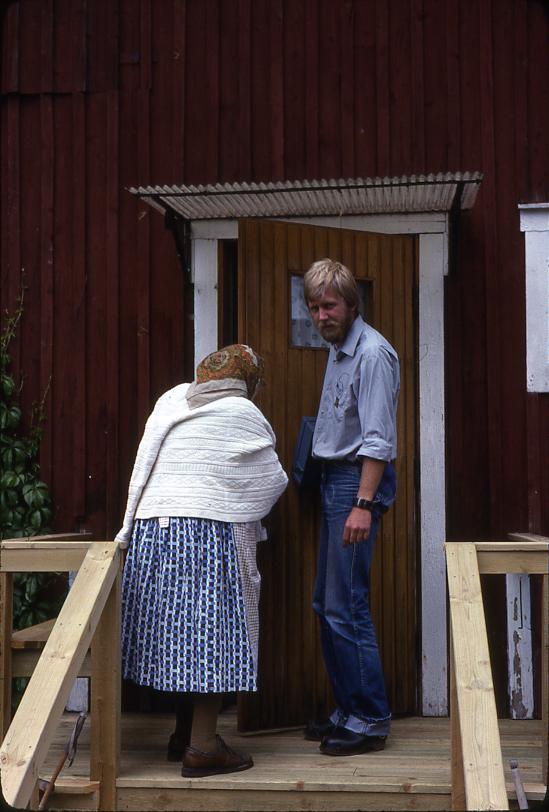 Lantbrevbärare Mikael Mattsson har kommit till Rockstaberg. Han står med Ester Gustavsson på trappan till hennes hus. De är på väg in genom dörren. Kassaskrinet har han under armen.