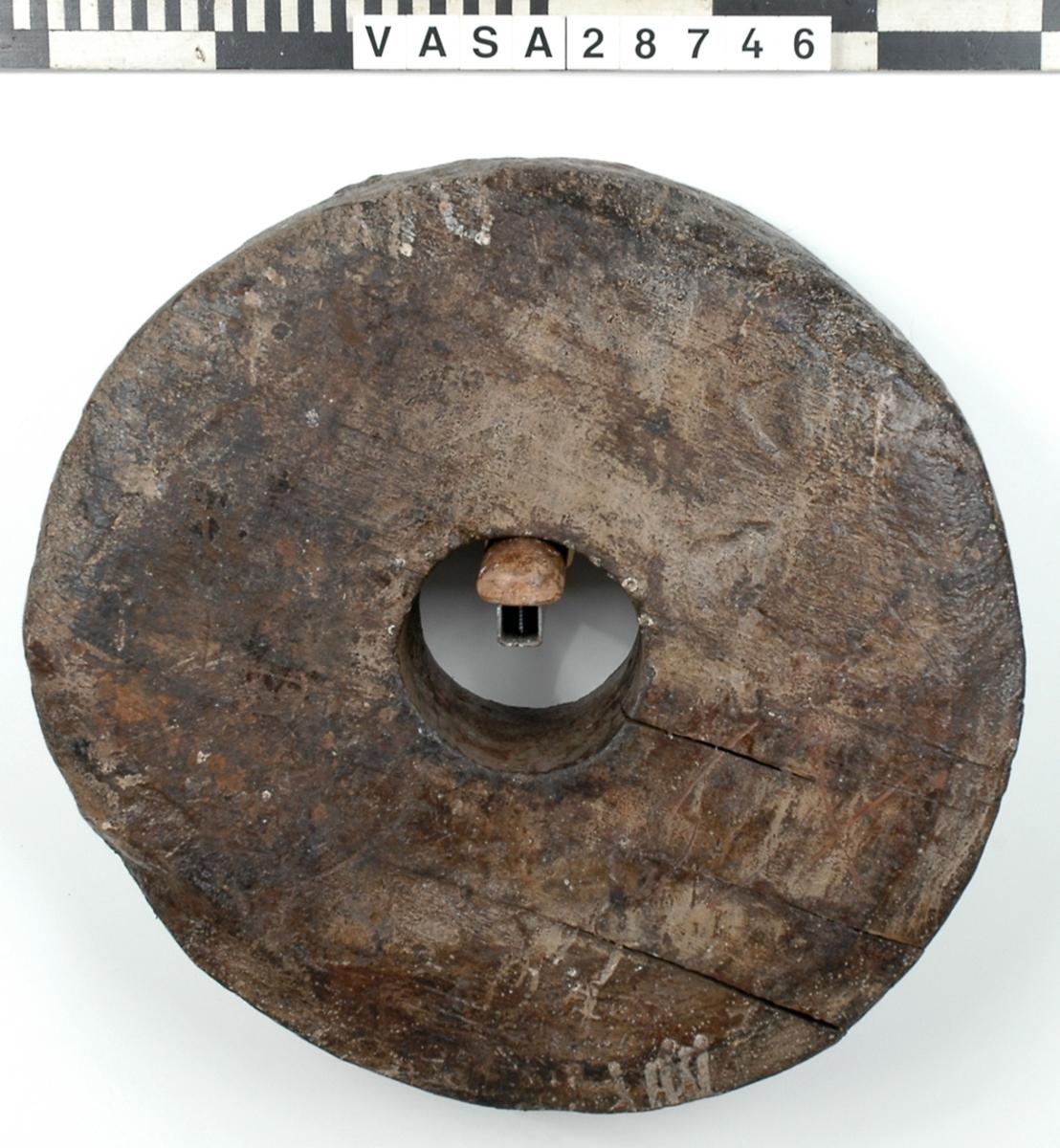 Lavetthjul. Båda sidor har en ca. 35 mm bred fasad kant. Ena sidan har haft en järnring runt hålet som suttit fast med 8 st spik. På samma sida som ringen suttit finns två träpluggar (30-35 mm i diam.) i hjulet.