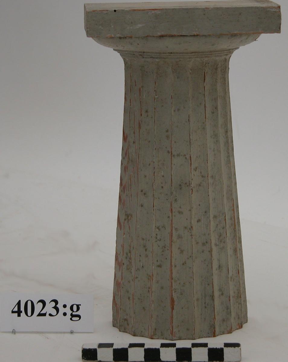 """Pelare, eller kolonner, släta och räfflade (7 st halvkolonner, räfflade). 20 st. modeller av trä, avsedda som fasadprydnader. Pelarna är räfflade med halvcirkelformig basyta. De är vitmålade. Kapitälen är av närmast dorisk stil. Pelarna utgör modeller till gavelkonstruktion för nya inventariekammaren på varvet 1785-87. De sammanhängs troligen med en serie av gavelmodeller och pelare, som finns i kistan i sal 1 och vid norra delen av väggen i samma sal. (K 2244)  Halvkolonn, kannelerad med kapitäl och fast abakus. Målad i gråvitt.  Märkt under abakus: """"6""""."""