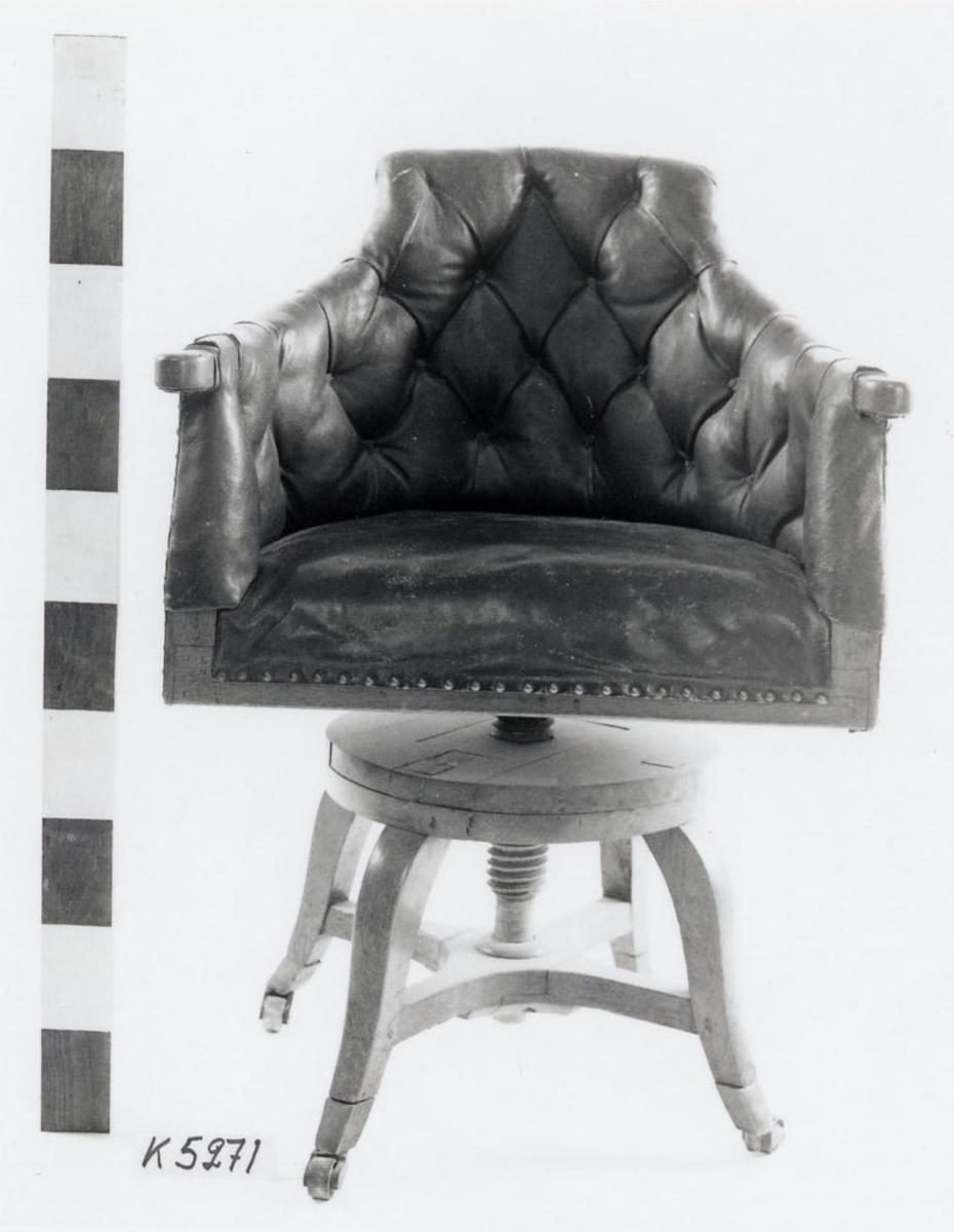 Stol, skrivstol av ek, med armstöd. Sits, ryggstöd och armstöd klädda med ryssläder. Underrede i trä med fyra svängda ben samt träskruv för höjning och sänkning av sitsen.