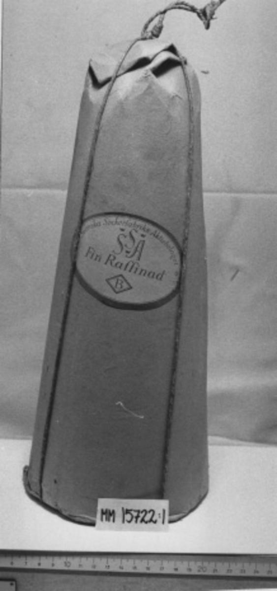 Sockertopp. Cylindrisk, med från basen konad så toppen är ungefär hälften av basens diameter. Sockertoppen är inslagen i grovt papper, ombundet med snöre. Oval etikett påklistrad med texten: Svenska Sockerfabriks Aktiebolaget Fin Raffinad.