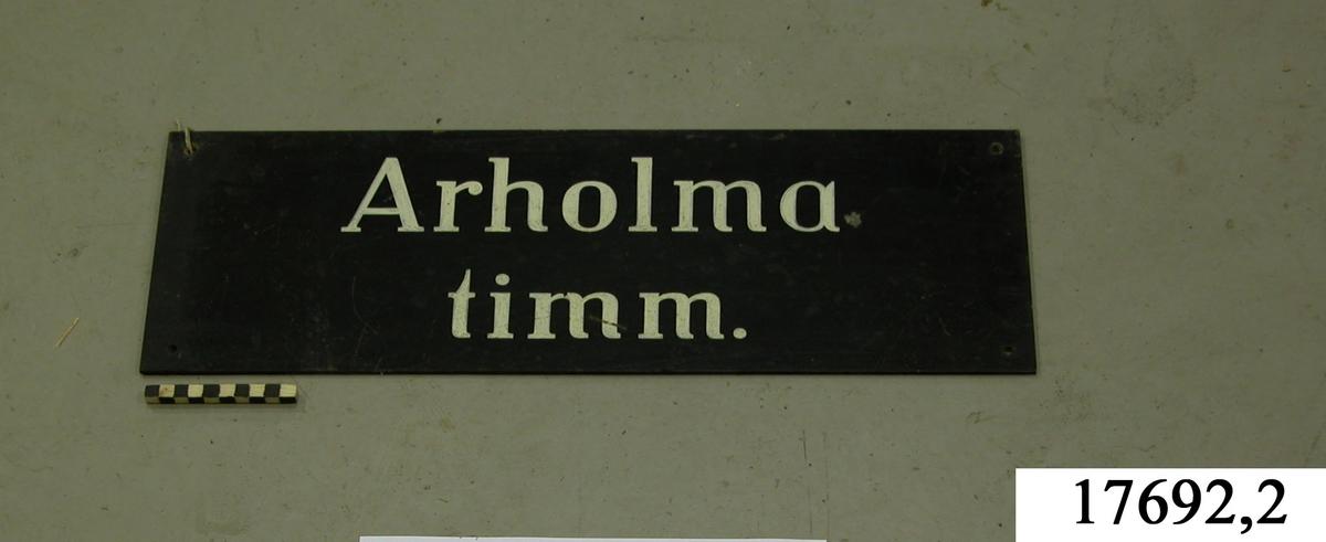 """Rektangulär skylt, framsidan svartmålad, hål för upphängning. Vit schablonmålad text: """" Arholma timm."""""""