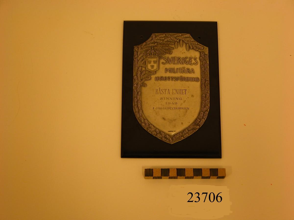 Plakett av silver i form av vapensköld fäst på platta av bakelit. Längs sköldens kant dekor föreställande granris samt tre hängande grankottar. I sköldens övre vänstra hörn en liten vapensköld med tre kronor, krönt med kunglig krona. Text på plaketten: SVERIGES MILITÄRA IDROTTSFÖRBUND BÄSTA ENHET SIMNING 1949 1 JAGARDIVISIONEN. Se SSS och X pärm.