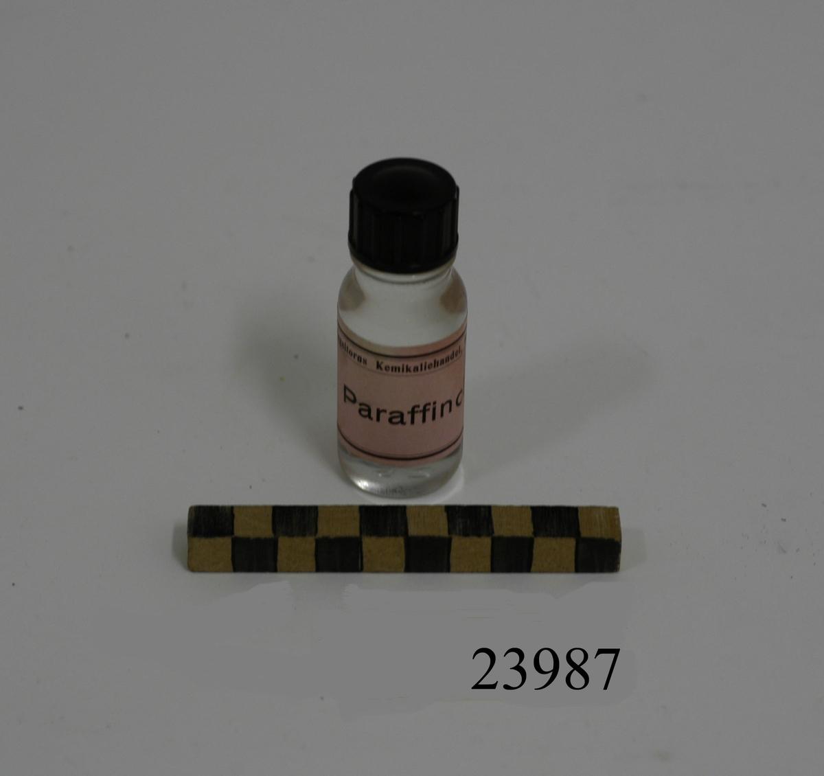 """Liten flaska av klart vitt glas med svart skruvkork av plast. Rosa etikett med text: """"Hageltorns Kemikaliehandel, Karlshamn. Paraffinolja"""". Innehåller Parafinolja. I botten """"25""""."""