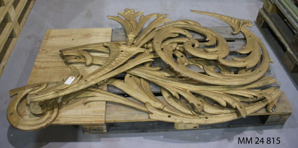Förstävsornament av förgylld plåt. Ingick i fartygets utsmyckning. Ornamentet består av 8 delar samt 1 sköld som var placerad i förstäven.