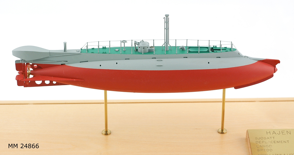 Ubåtsmodell Hajen i monter. Modell av alträ med detaljer av mässing, målad med cellulosafärg. Rött och grått skrov. Monter av plexiglas på träplatta. Mässingsbricka i montern med uppgifter om modellen.