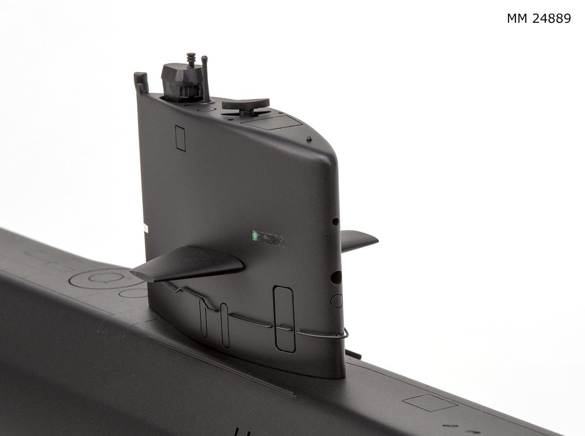 Ubåtsmodell Näcken stirling i monter. Modell av alträ med detaljer av mässing, målad med cellulosafärg. Svart skrov. Monter av plexiglas på träplatta. Mässingsbricka i montern med uppgifter om modellen.