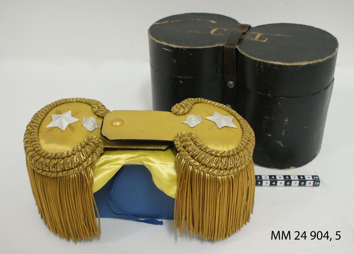 """Epåletter, 2 st, i pappask till paraduniform i flottan. Epåletterna av kläde med fransar av guldtråd. På översidan stjärna av silver och däröver kunglig krona av silver (finns märken som tyder på att epåletten haft ett annat märke fastsytt tidigare. Gulfärgad knapp med ankare. På undersidan en svart säkerhetsnål samt hake för fastsättning. I asken finns dessutom två hängslen av svart tyg med guldtyg på översidan och med knäppning till axelklaffarna. Epåletter med tillbehör förvaras i svart pappask med text i guld: """"C.G.L."""". Brun läderrem med spänne låser fast locket i asken. På lockets insida finns texten: P. Huldt, Sundsvall"""" skrivet. Asken är invändigt blå. I asken finns även kuddar i gult tyg som skydd för epåletterna."""