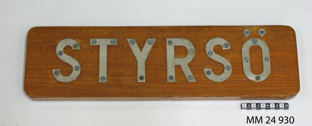 """Namnbräda av fernissad teak. Bokstäver av stål fastskruvade från framsidan, bildar namnet: """"Styrsö""""."""