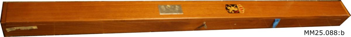 """Rektangulär trälåda i mörkt fernissat trä. Lådan är försedd med lock och lås. På lådans lock finns en målad vapensköld med en get som står på bakbenen. Vapnet försett med krona. Längre ner sitter en metallskylt med två korsade flaggor, flankerade av två vapensköldar, samt text """"Jagaren Hälsingland 1959"""" ingraverat."""