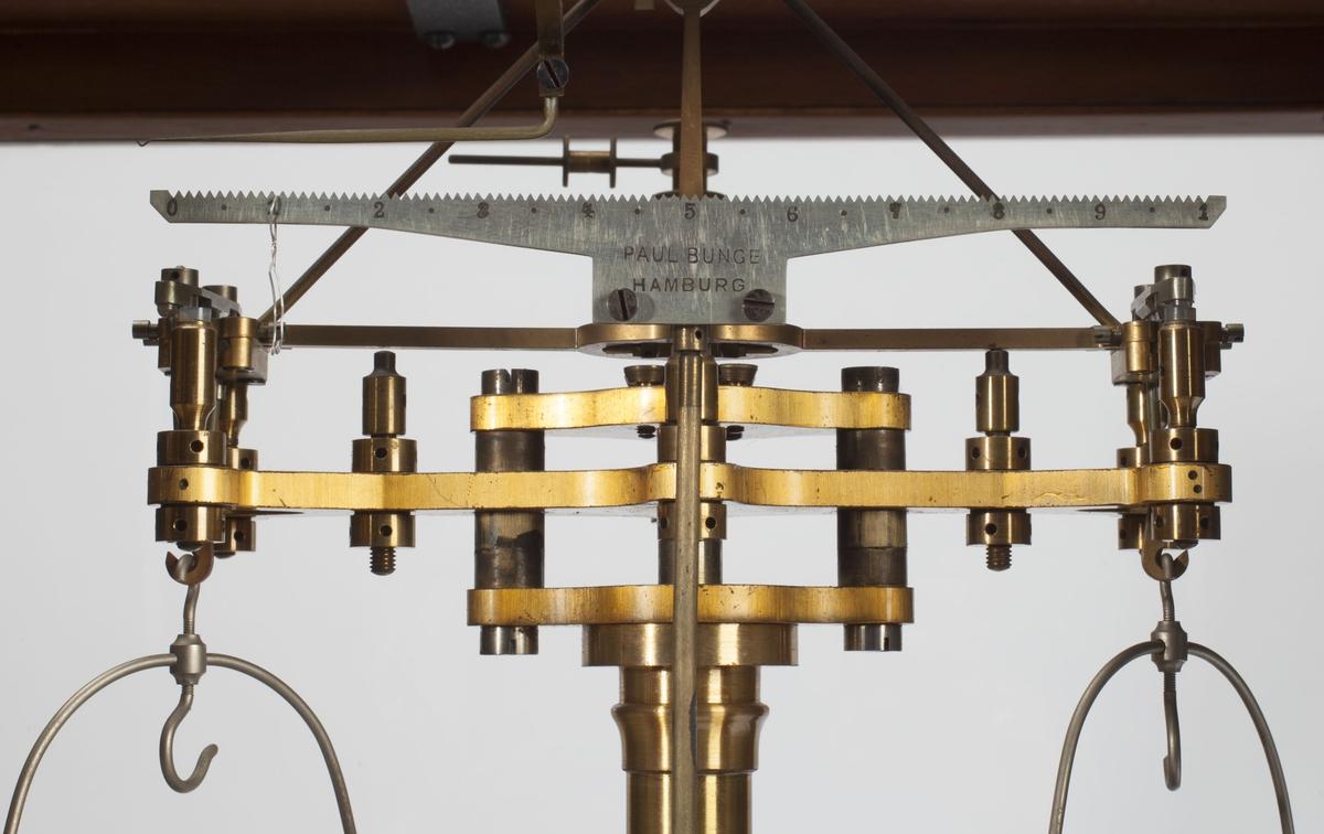 Vekten har to stykk to-veis kniver, to oppheng, to skåloppheng og to skåler. De to langsidene i huset kan dras opp og reguleres trinnvis. De to andre sidene er dører som åpnes utover. I lokket er det felt inn en glassplate.  Vekten har to bein som kan stilles, disse kalles skruer for watring, de stilles inn før bruk, slik at loddet bak henger henger rett over spissen. Det er en skrue nær toppen av vekta som flyttes til vektarmene henger riktig. Det ser man når utløsersveiva nede under glassplata blir brukt: da vil både vektarmene og skålene frigjøres til bruk. Oppe under taket er en skrue som styrer en arm til påheng av små loddsatser når vekta brukes, for å regulere selve vekta.  Kilde: Beretning om Mynt-Kontrollkommisionens anden undersøgelse af Myntens Balancer og Lodder 1877.