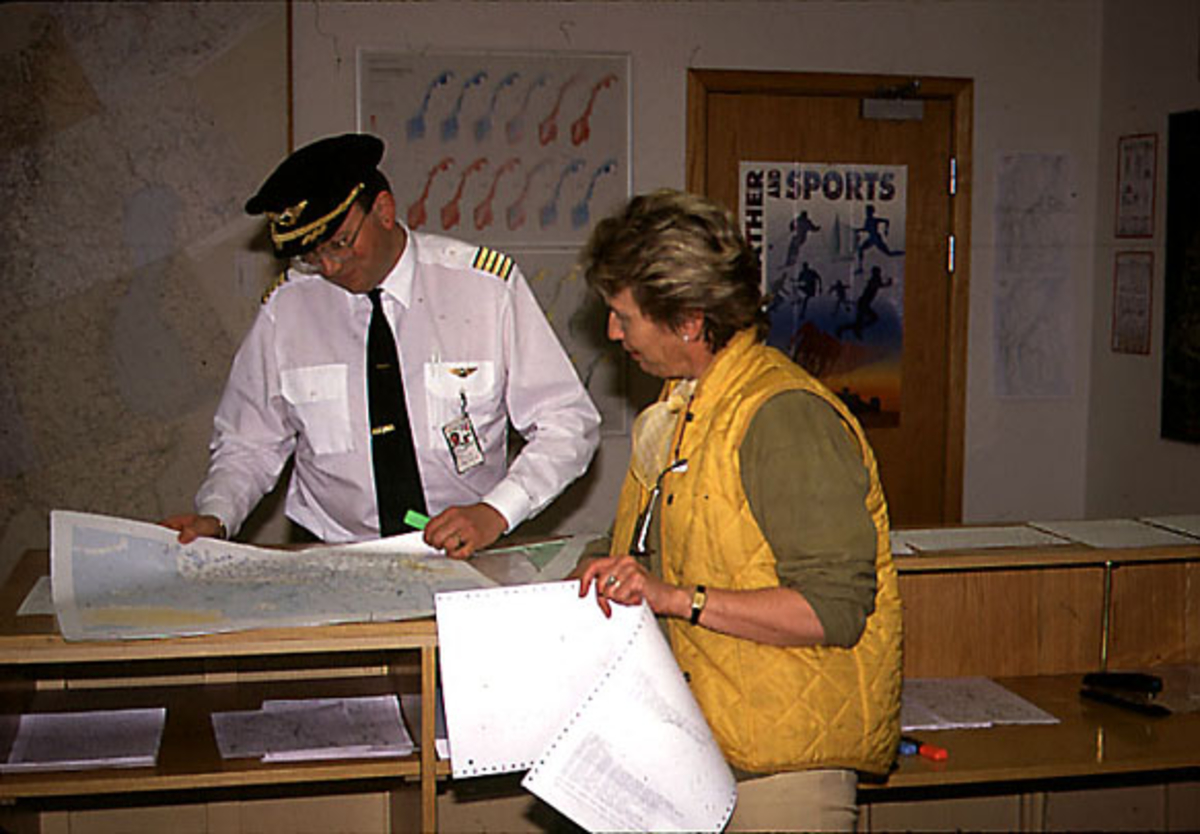 Lufthavn, portrett av 2 personer, en i flyuniform, studerer et kart, tatt innendørs.