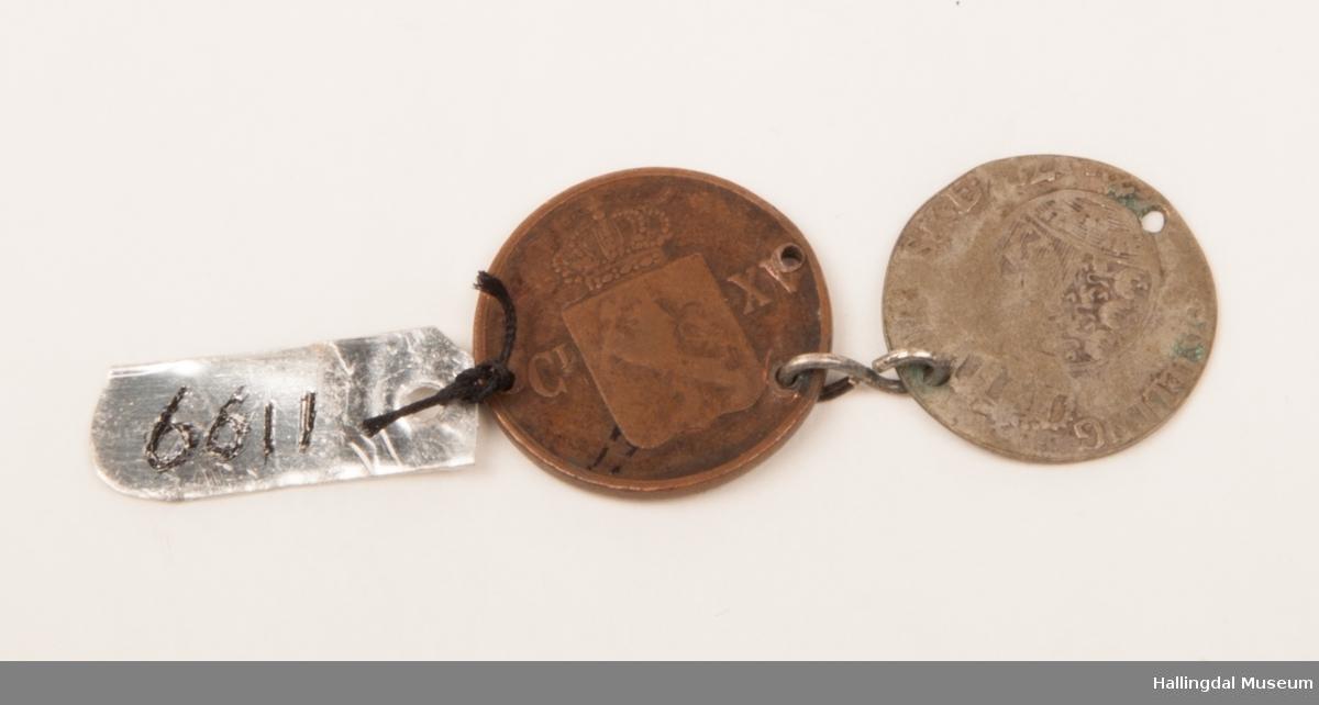 2 mynter henger sammen, del av et kjede.  Holdt sammen av 8-talls formet sølvtråd.  1 sølv 4-skilling, da., 1 1/2 skilling kobber 1863, sv.