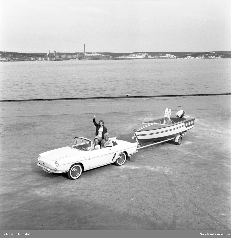 En nercabbad sportbil med en motorbåt på släpvagn bakom. Förare och passagerare vinkar glatt.