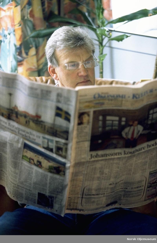 Mann sitter og leser Aftenposten, økonomi-kultur-sport, ombord på Frigg boligplattformen QP