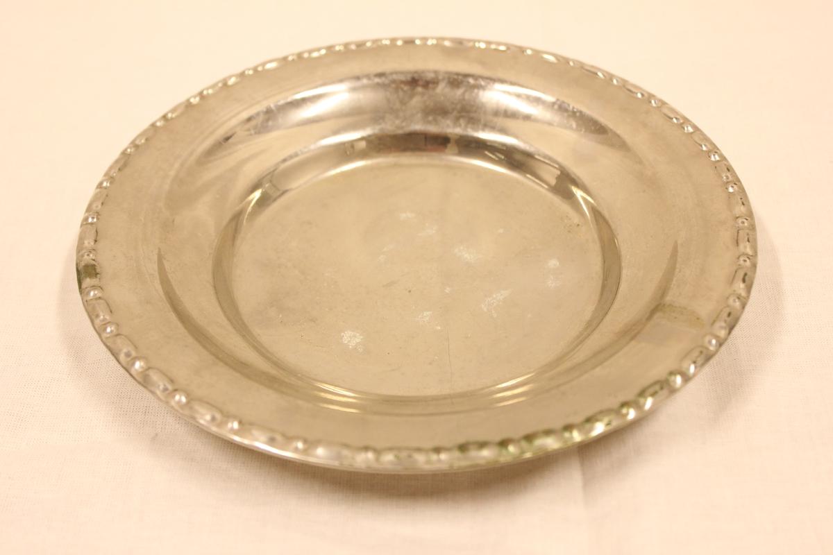 Et lite fat i sølvplett med en preget bord ytterst.
