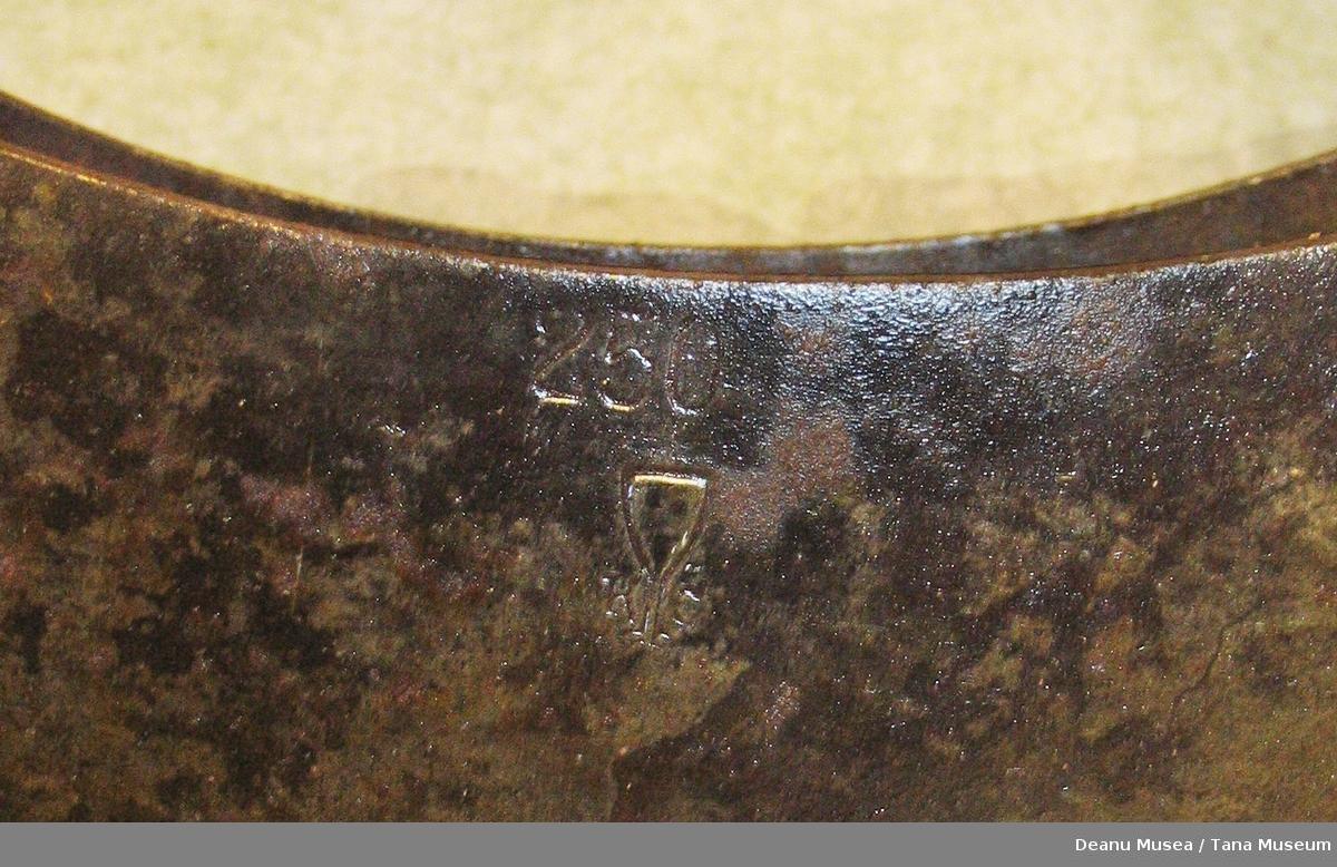 """Kniven har to blader. Knivbladene er buet og holdes sammen av håndtaket. Stempel på det ene knivbladet som viser  """"250"""", og et vinglass med """"K"""" og noe som likner et skjold på hver side av stetten."""