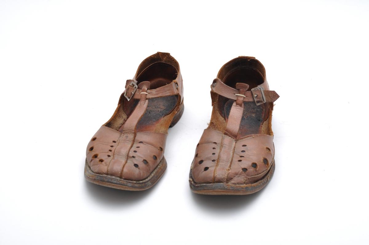 Sandal i brunt naturfarget lær. Lav hæl, reim og spenne. Velbrukt. Dekortivt hullmønster i overlær.