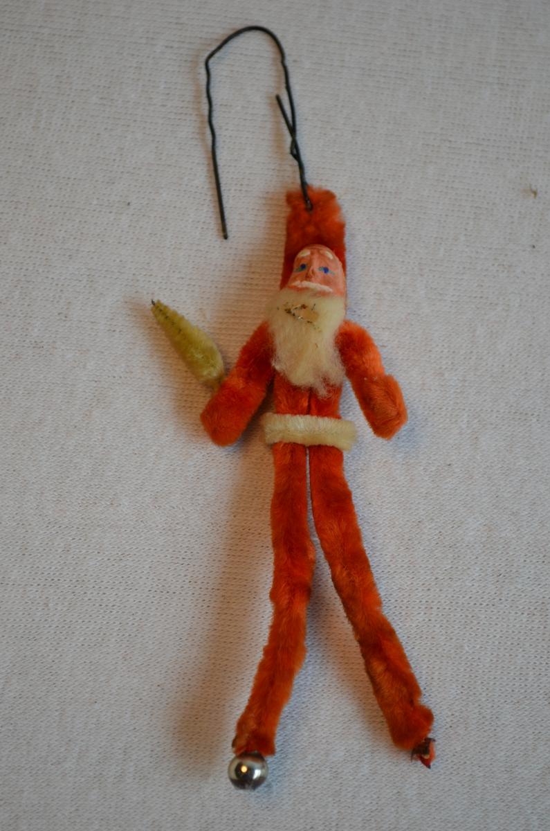 Julenisse med juletre laga av piperensarar med porselensansikt. Juletreet er veldig falma og er meir gul einn grøn. Raudfargen er også falma. Festa med ståltrå i nissehua.